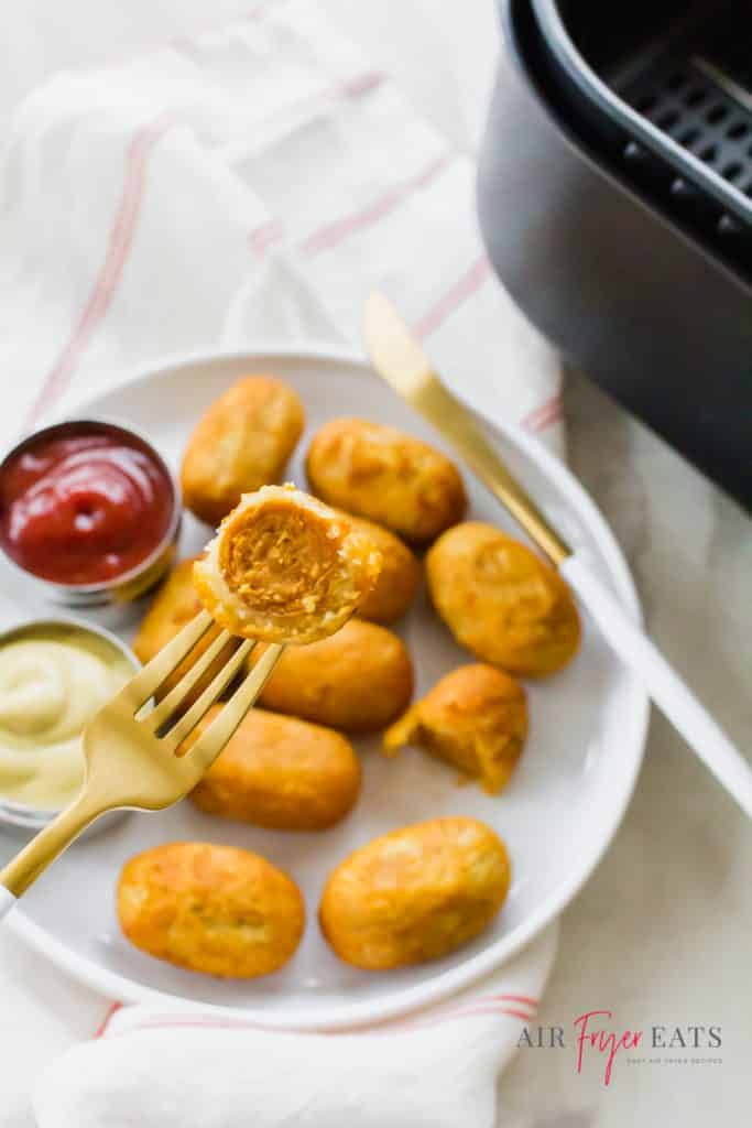 mini corndogs on a plate with ketchup being eaten with a fork.