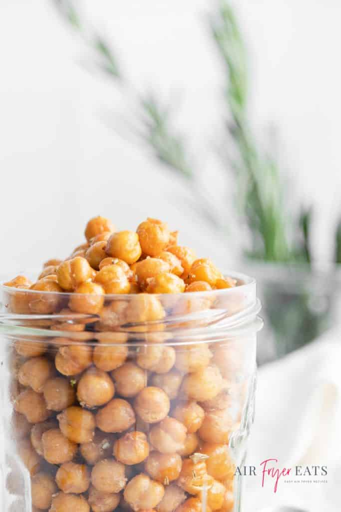 closeup view of a jar of roasted chickpeas with rosemary