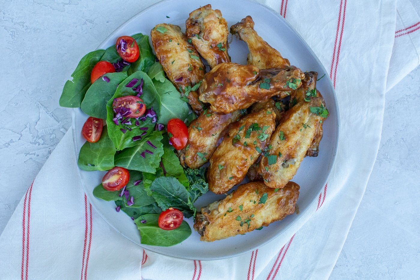 A pile of glazed chicken wing pieces aside a green salad with small red tomatoes and bits of red onion on a white plate