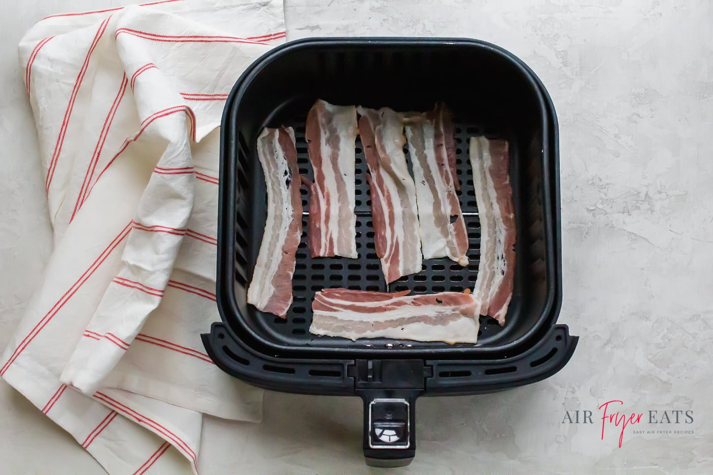 raw pork bacon laying in an air fryer basket with a red and white towel to the left of the basket