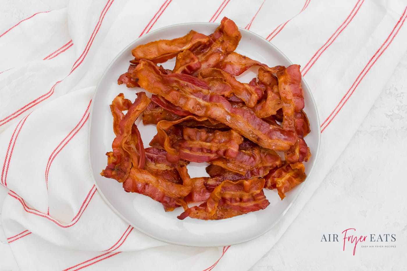 a large pile of crispy brown bacon pieces on a white plate over a striped red and white towel