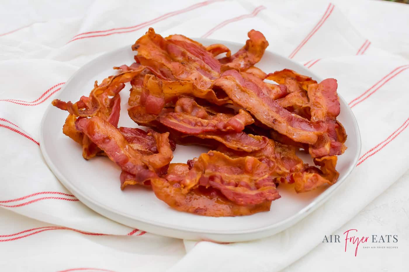 a pile of bacon pieces on a white plate on top of a red and white flour sack cloth