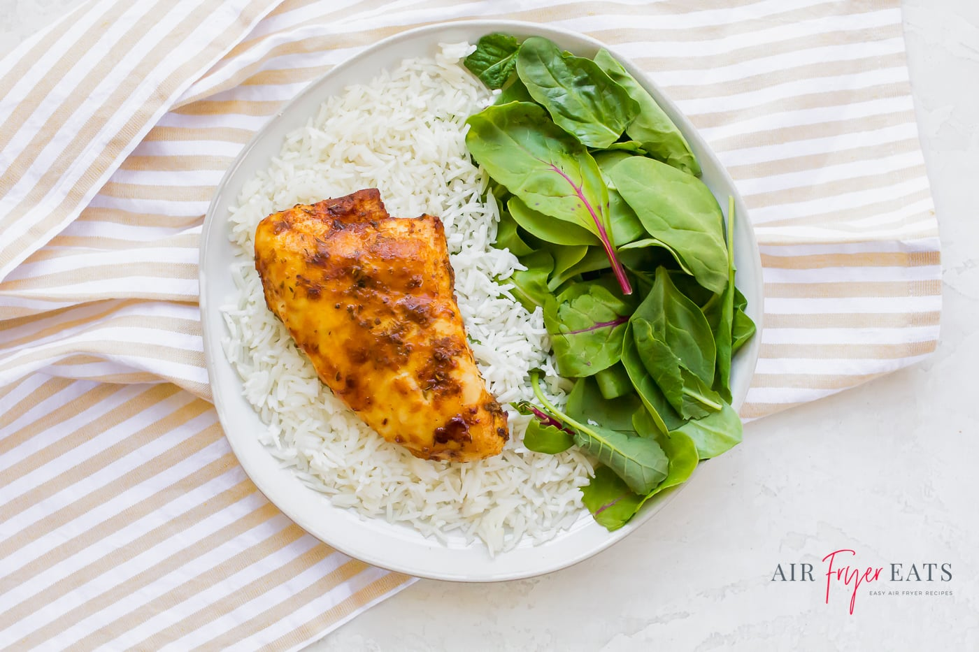 A single chicken breast on a white plate with steamed white rice and a generous helping of fresh spinach