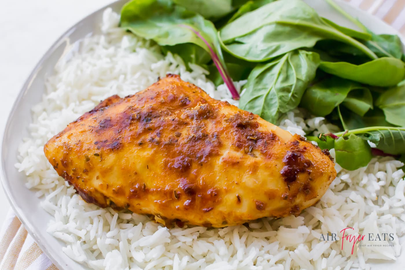 A browned skinless chicken breast on a bed of white rice with fresh greens