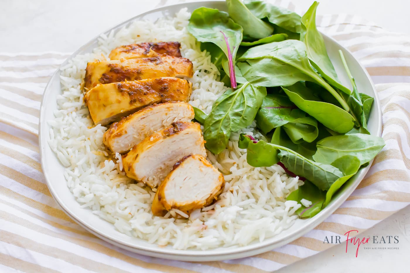 a white plate with a bed of fluffy white rice topped with a sliced chicken breast aside bright green spinach leaves