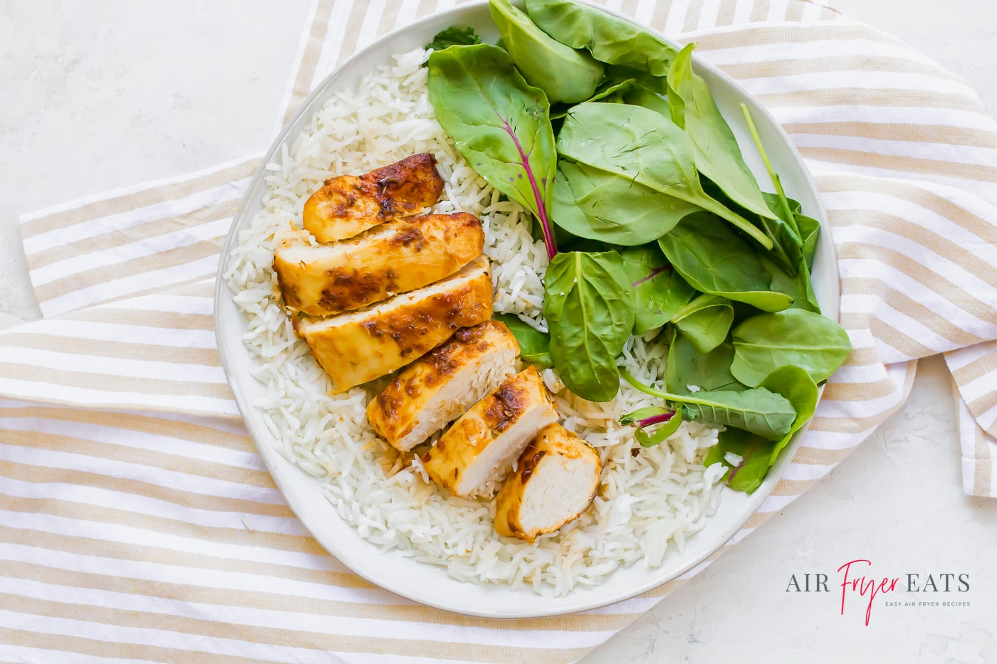 A sliced browned chicken breast arranged over a plate of white rice aside a pile of fresh spinach