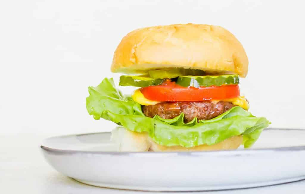 a cheeseburger on a light tan bun with green lettuce, a red tomato slice, and a few slices of green pickle