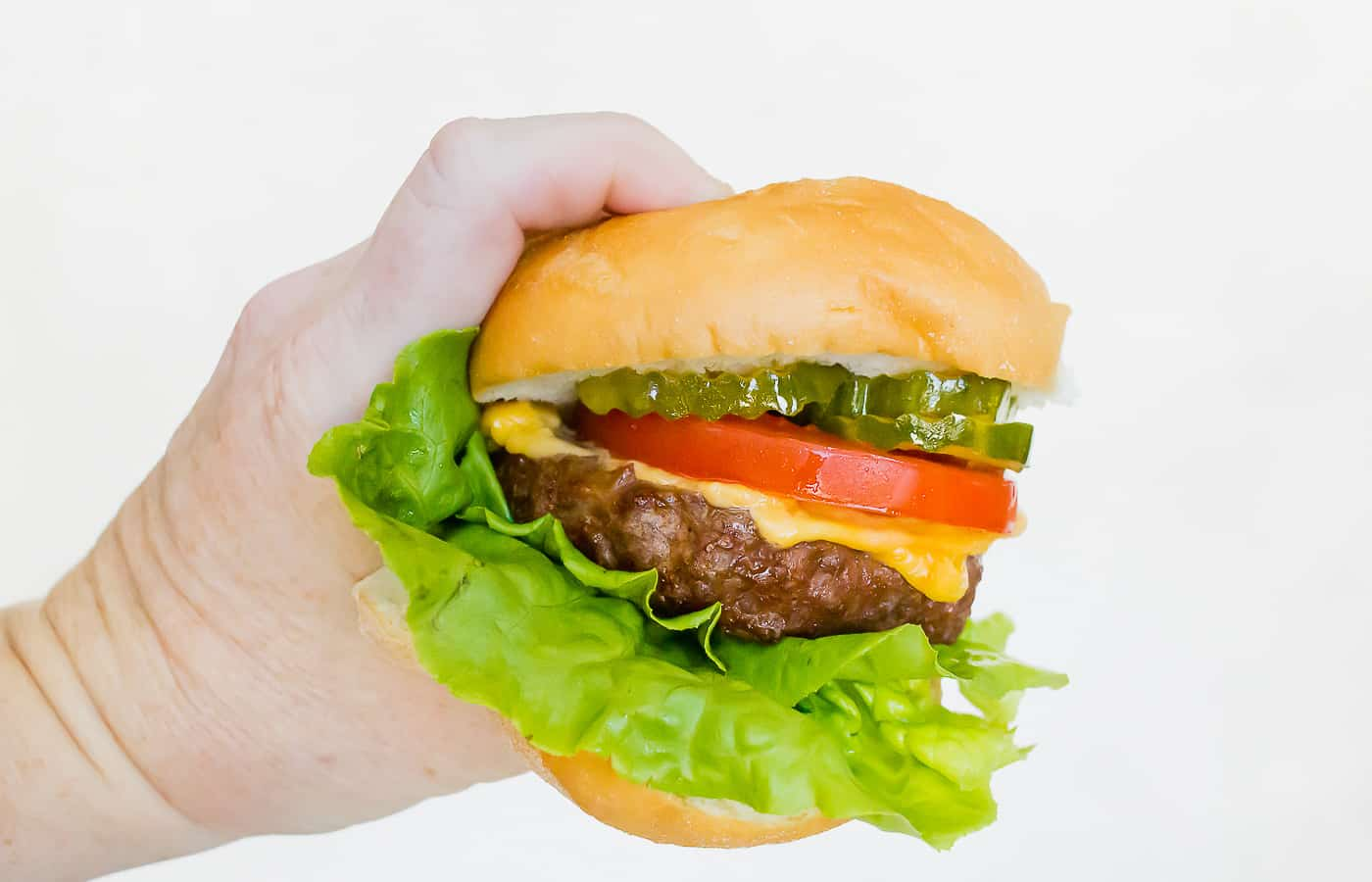 a hand holding a cheeseburger with lettuce, tomato, and pickles on a tan bun