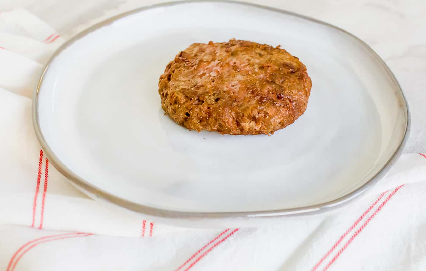 a cooked round hamburger patty on a round white plate