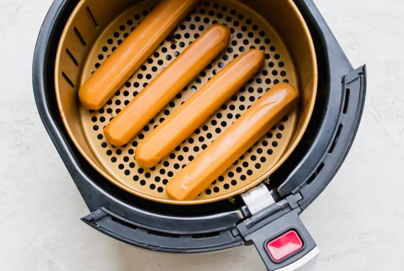 four uncooked hot dogs in the bottom of a round air fryer basket