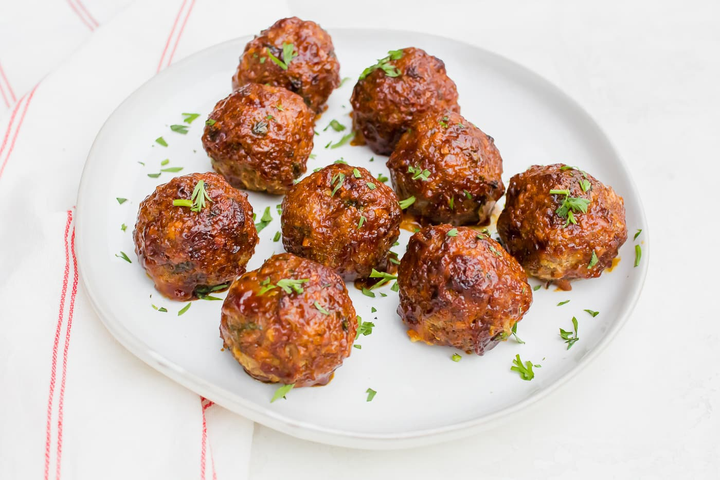 meatballs glazed with a brown-orange sauce and sprinkled with bright green herbs on a white plate