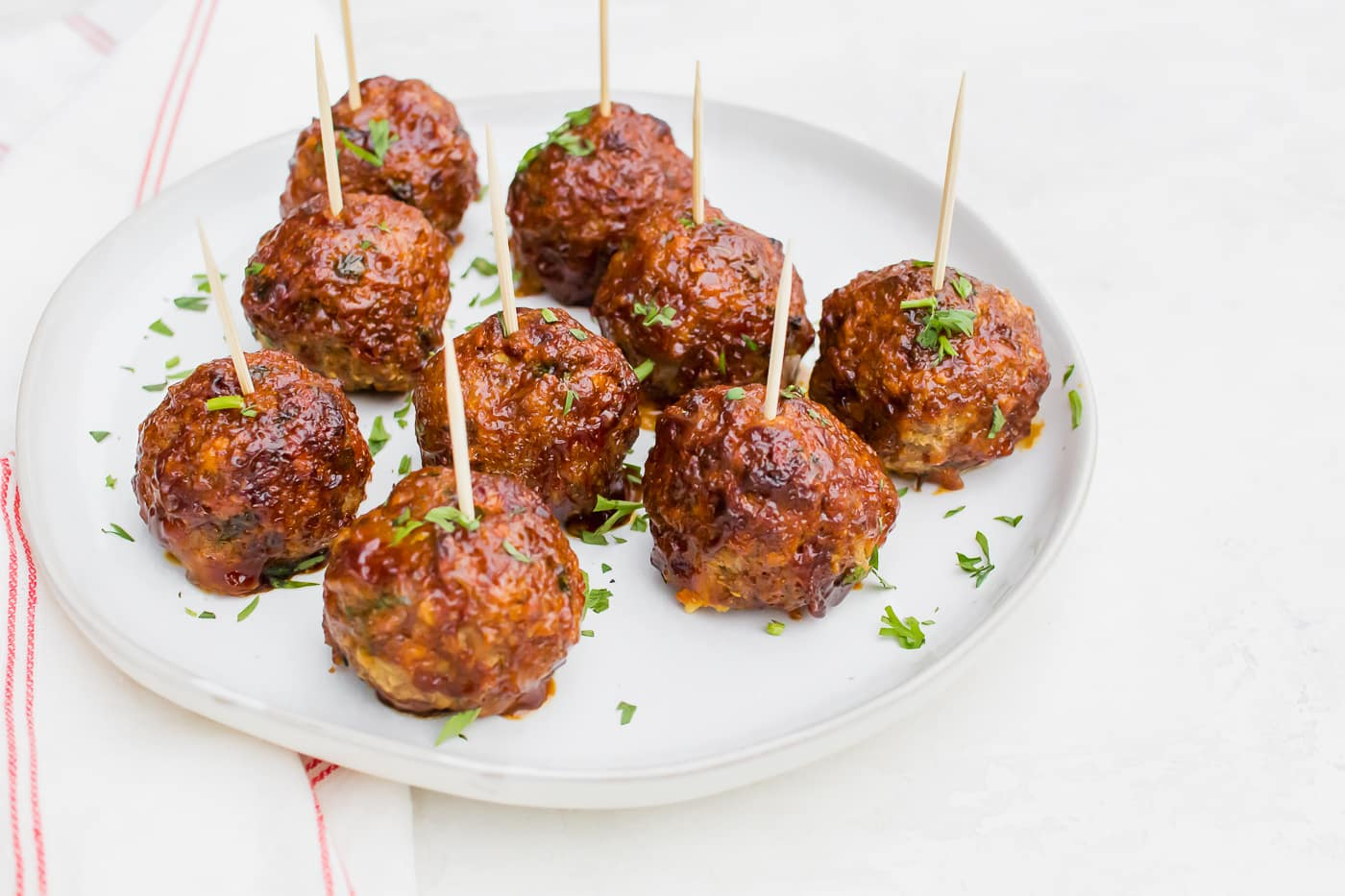 skewered meatballs with a brown glaze and fresh parsley on a bright white round plate