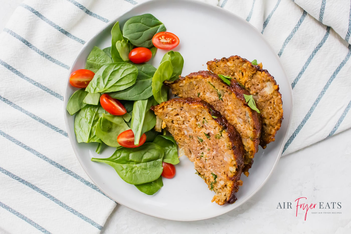 slices of meatloaf topped with herbs and arranged beside a spinach and tomato salad on a white plate