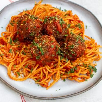 a pile of spaghetti and four meatballs covered in red sauce with fresh herbs on a round white plate