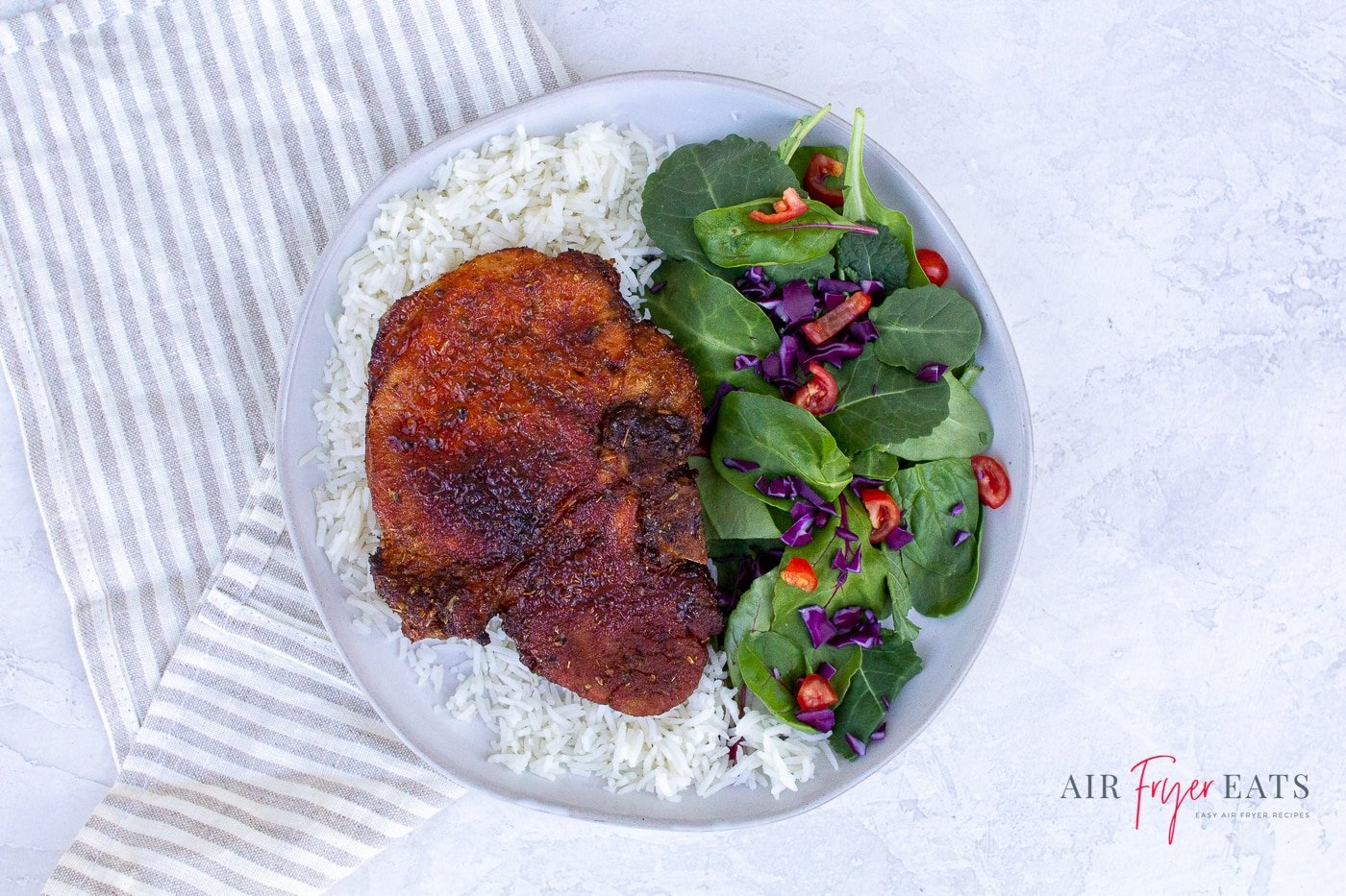 a browned porkchop over a bed of rice with a side salad on a white plate