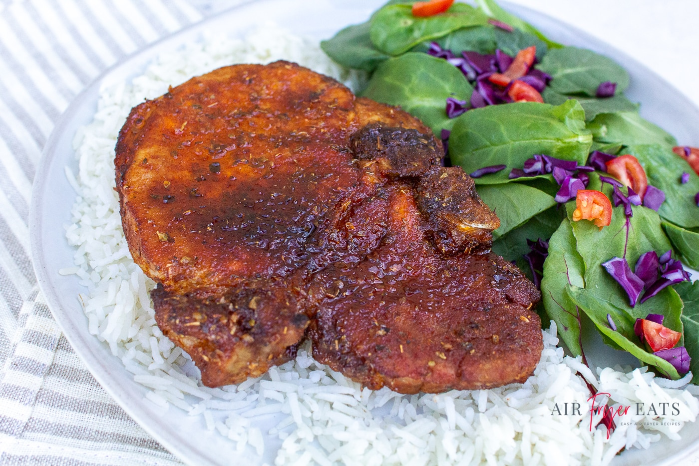 a pork chop with a crispy brown crust aside a spinach and vegetable salad served with fluffy white rice