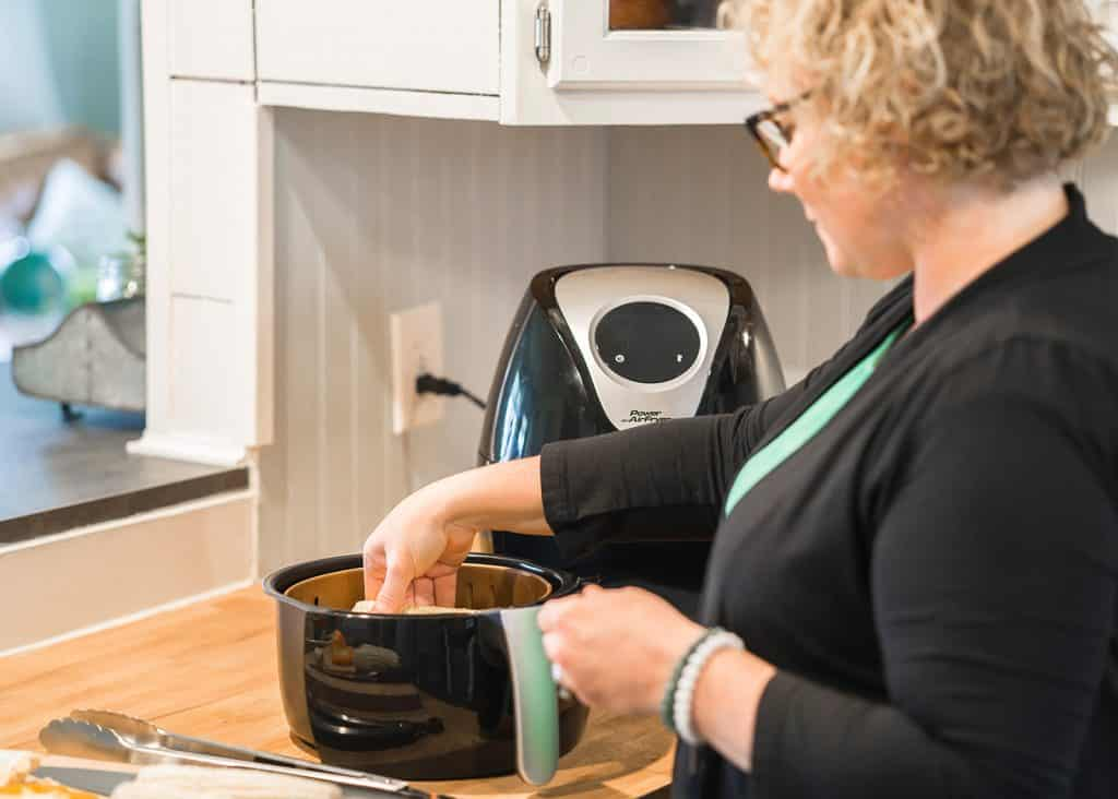 air fryer start here, picture of cindy gordon from airfryereats.com putting corn into an air fryer basket