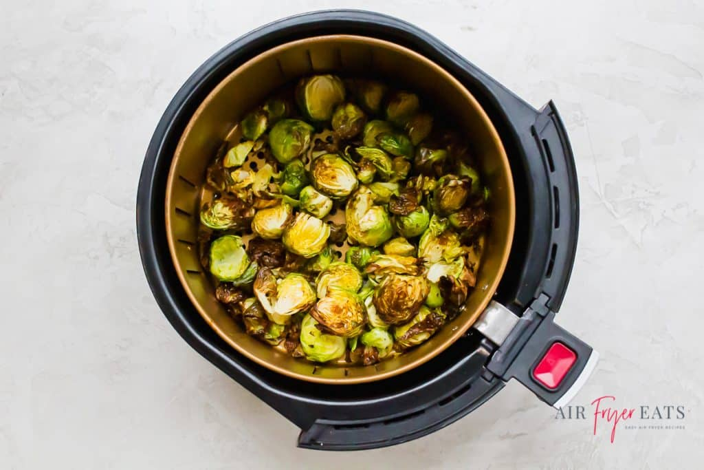 a round air fryer basket filled with air fried browned brussel sprouts