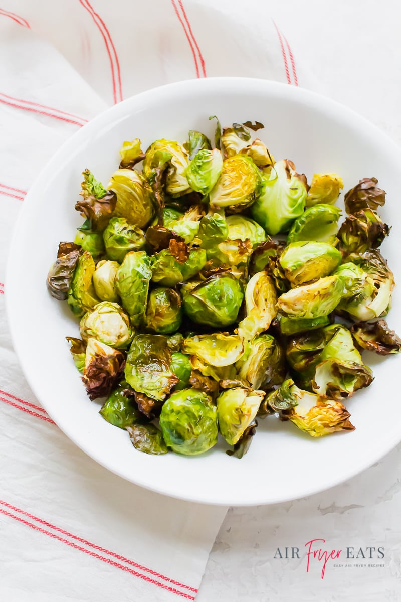 roasted brussels sprouts in a white bowl over a red and white striped towel