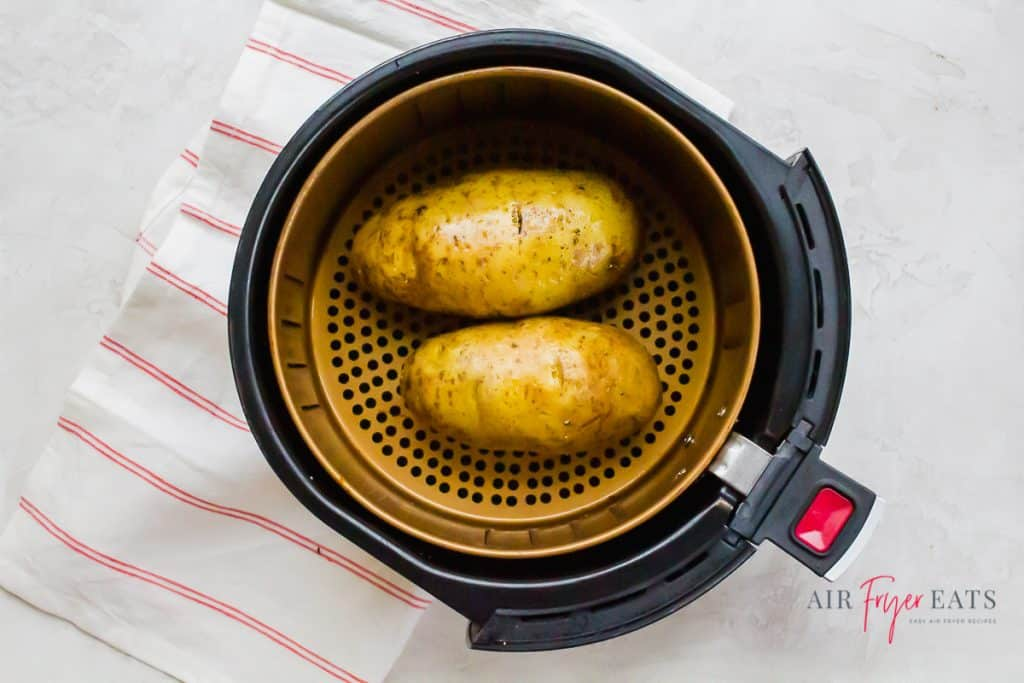 two brown russet potatoes in a round air fryer basket