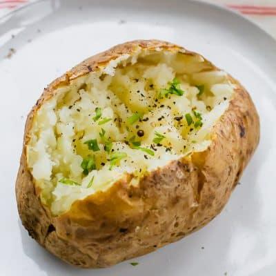 an air fryer baked potato split in half with herbs sprinkled overtop
