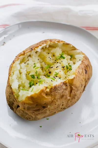 an air fryer baked potato split in half with herbs sprinkled overtop