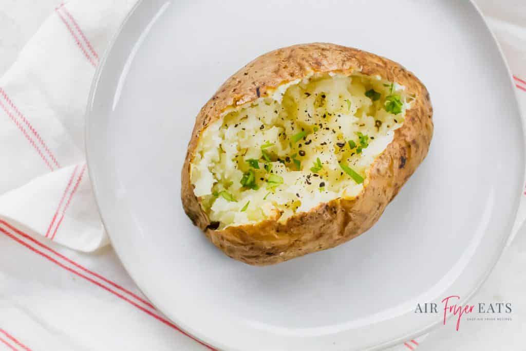 a baked potato split with black pepper and green herbs on a white plate