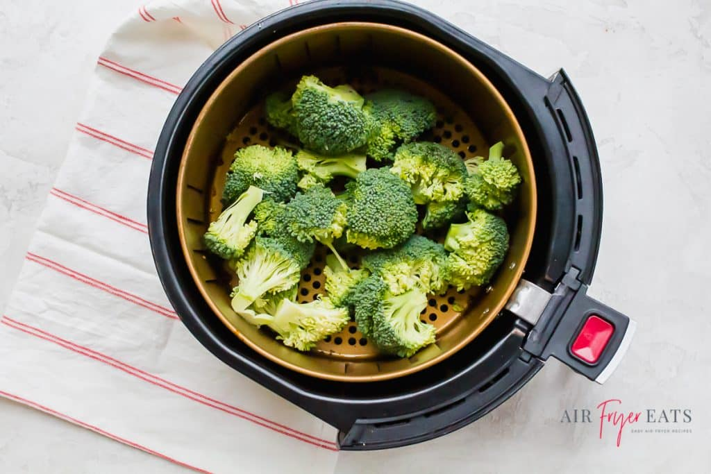 fresh broccoli florets in the basket of an air fryer