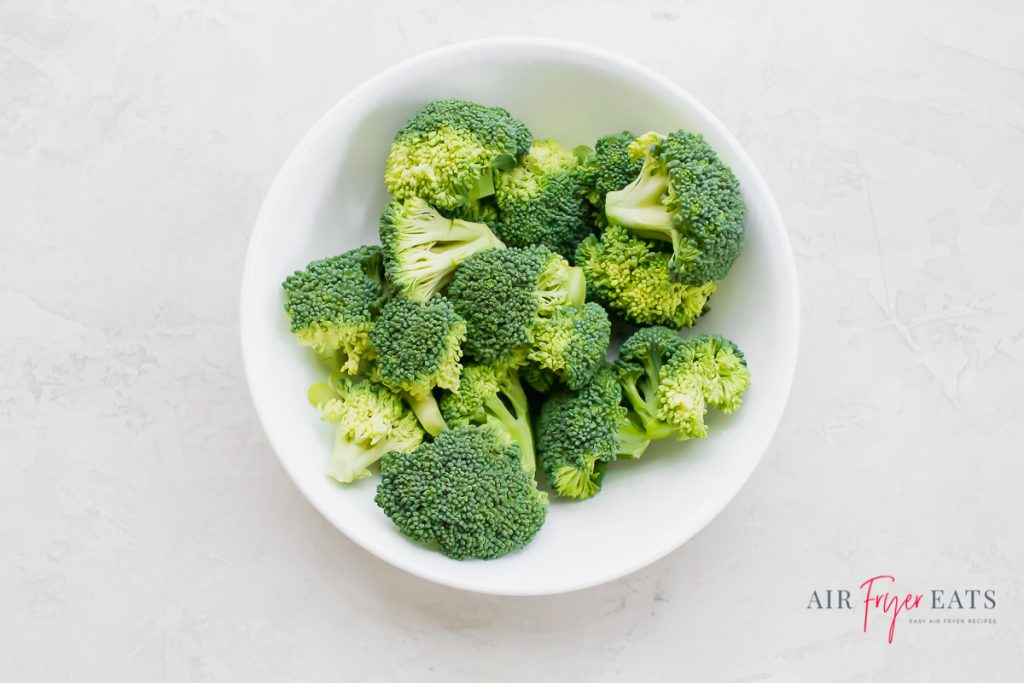 green raw broccoli in a white bowl on a white background