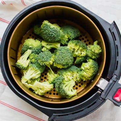 a pile of broccoli in the basket of an air fryer