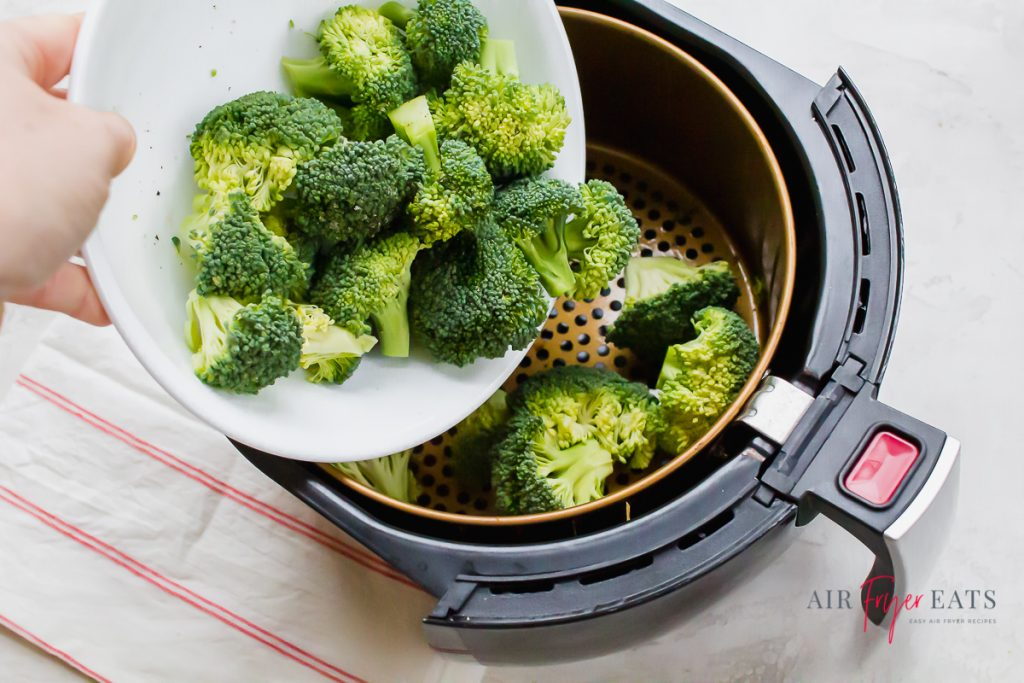 a hand pouring broccoli florets from a white bowl into the basket of an air fryer