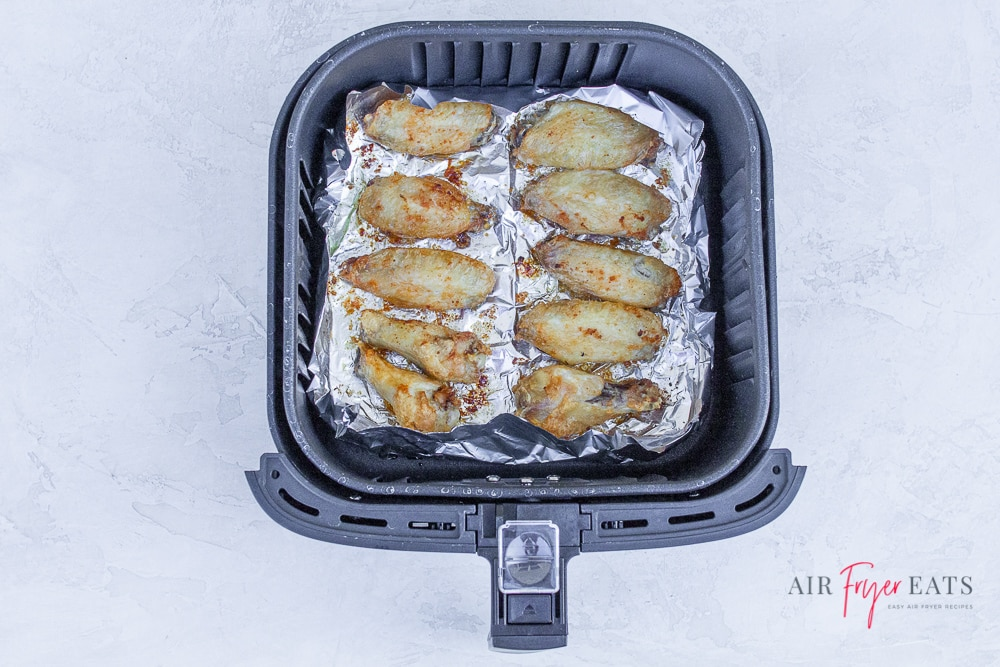 10 brown chicken wing pieces in a foil lined air fryer basket