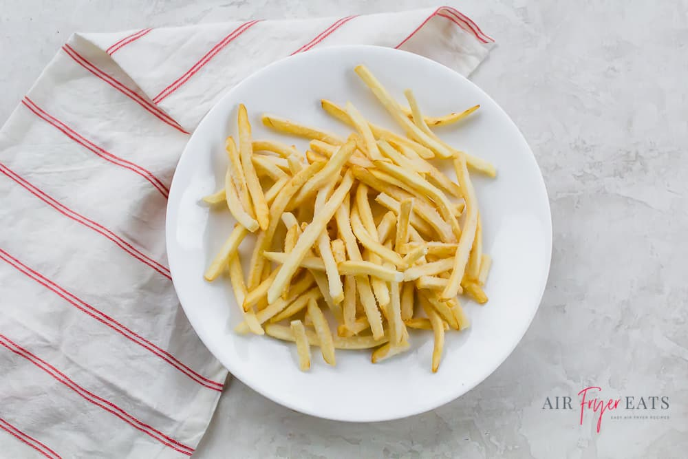 a pile of french fries on a round white plate over a red and white striped towel
