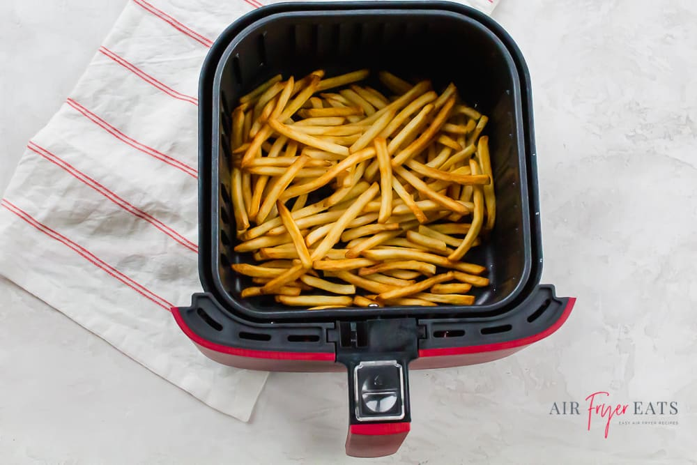 cooked fries in the square shaped basket of a red air fryer