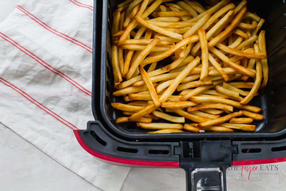 fresh cooked golden brown french fries in an air fryer basket