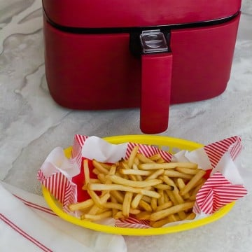 a yellow basket of cooked french fries beside a red air fryer