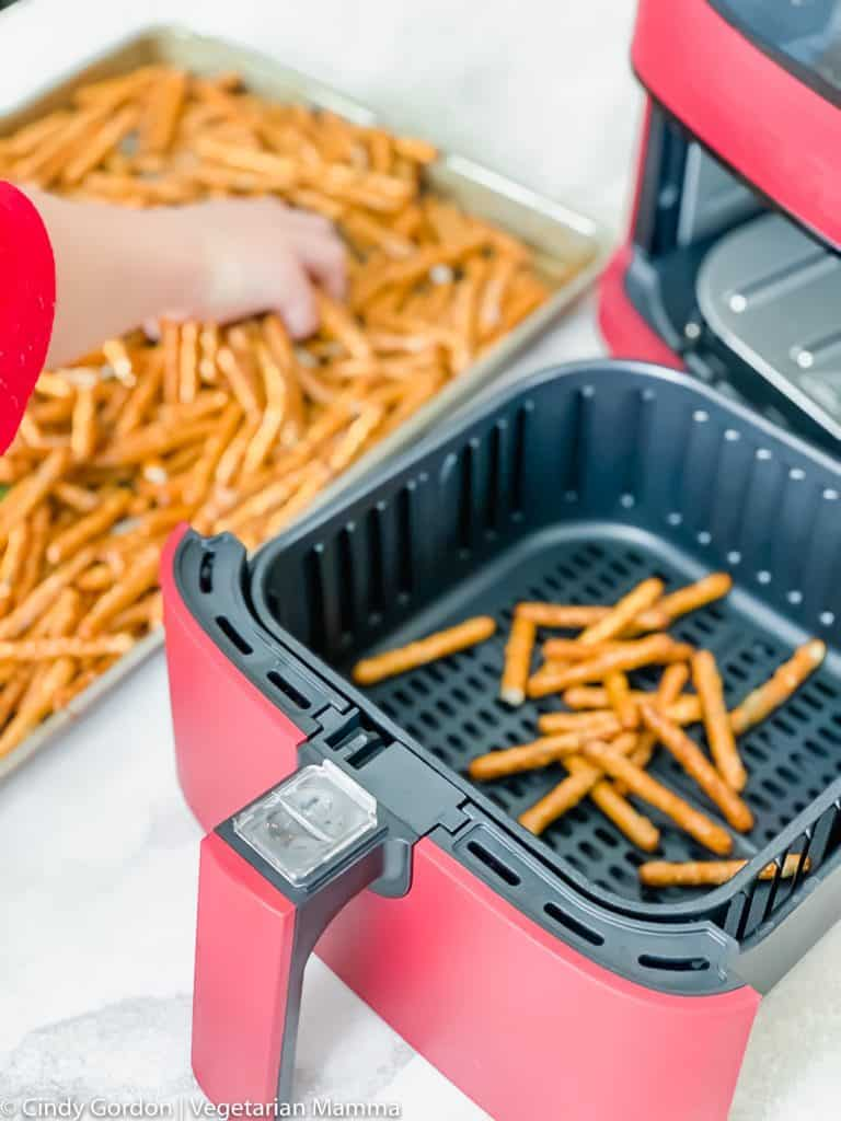 hand on the left grabbing pretzels from a cookie sheet. On the right is a red and black air fryer unit. Some pretzels in the air fryer basket
