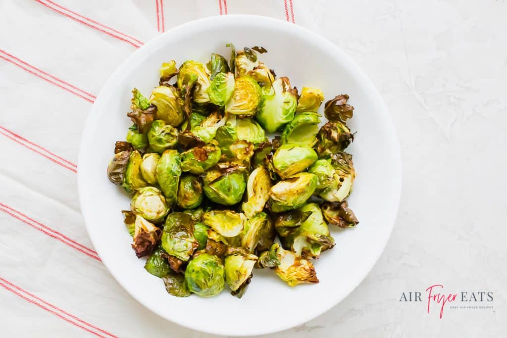 cooked air fryer brussel sprouts on a round white plate