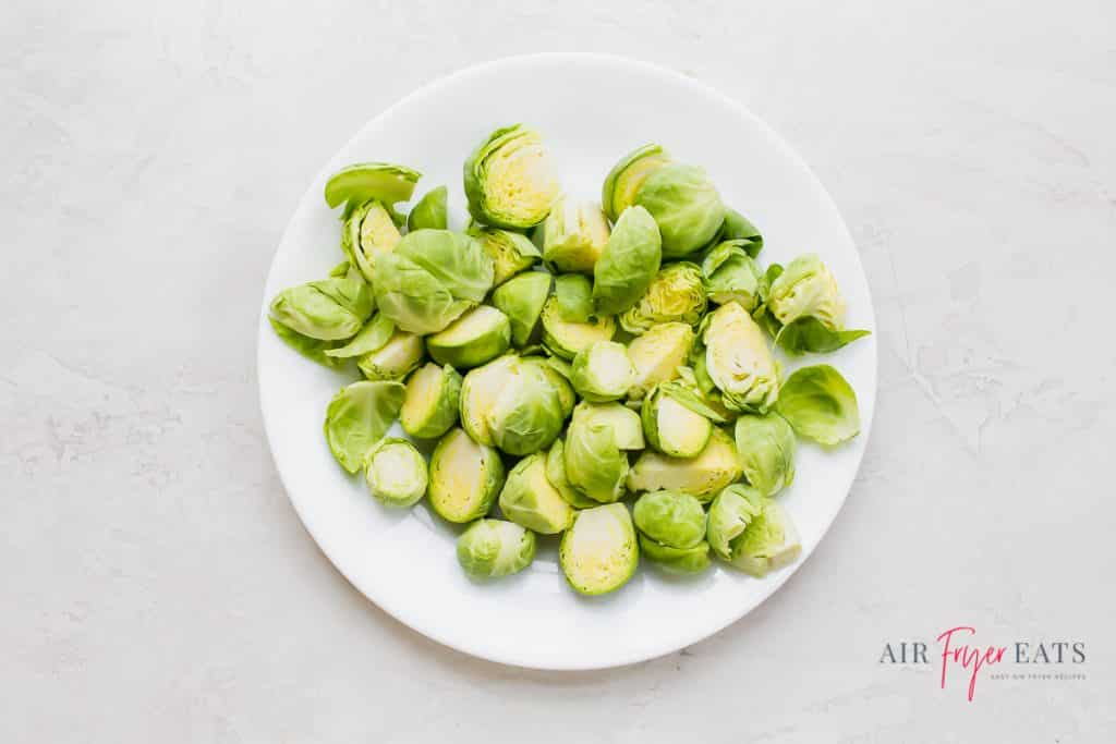 a white plate full of uncooked brussel sprouts cut in half