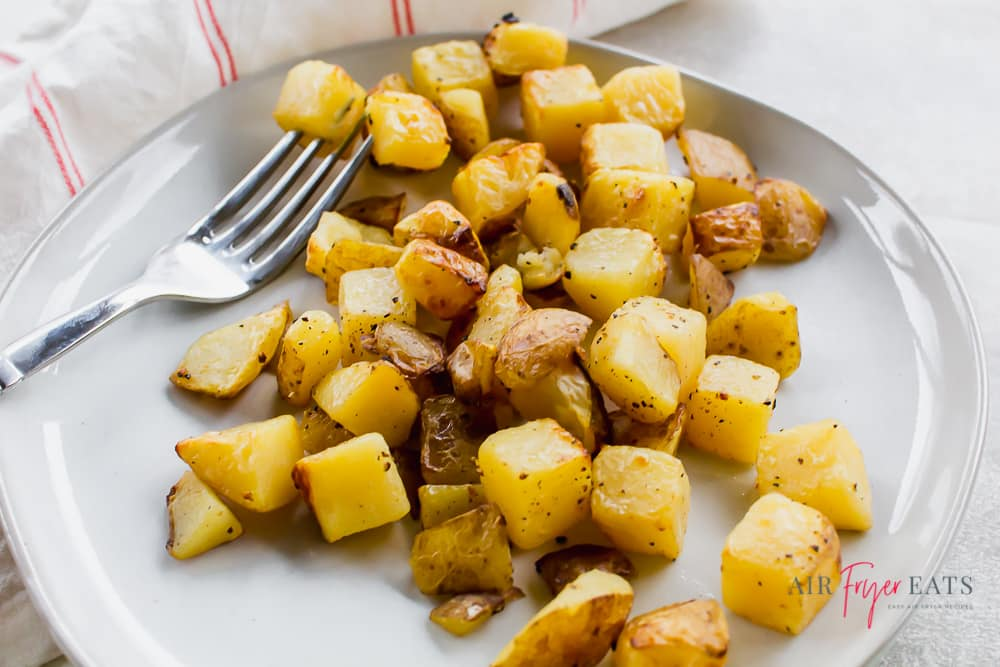 Close up shot of golden brown seasoned potato cubes on a white plate with a fork.