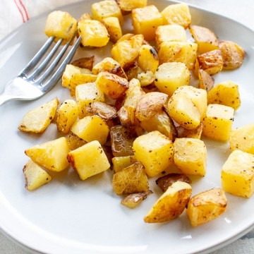 Crispy golden brown air fried potatoes on a white plate with a fork