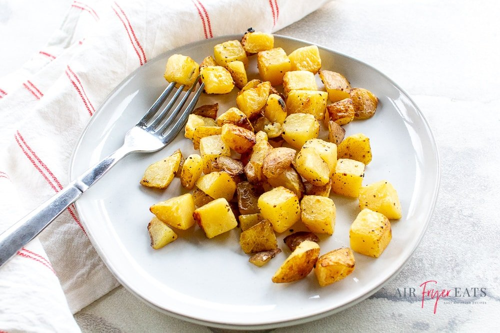 landscape style photograph of white plate with golden brown potatoes cubes on it along with a silver fork.
