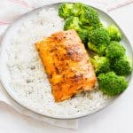a fillet of cooked salmon on a round plate with rice and broccoli