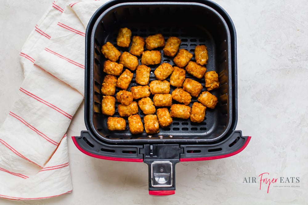 a square air fryer basket filled with tater tots