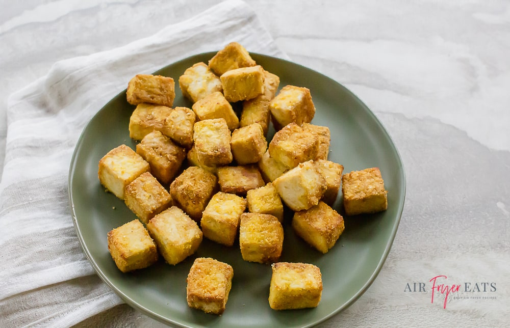 a pile of brown air fried tofu bites on a gray plate