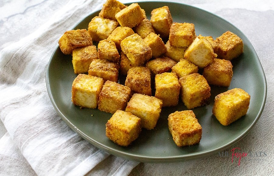 cooked light brown colored cubes of tofu on a gray plate
