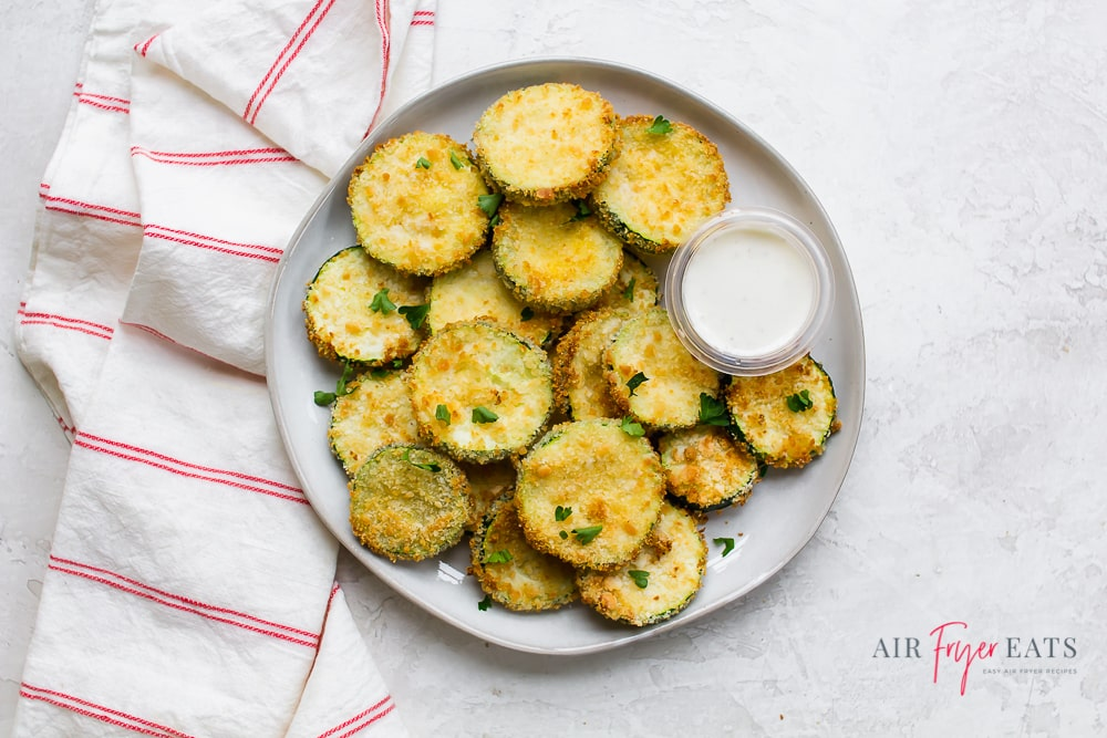 fried round slices of zucchini with a cup of ranch dressing on a round plate