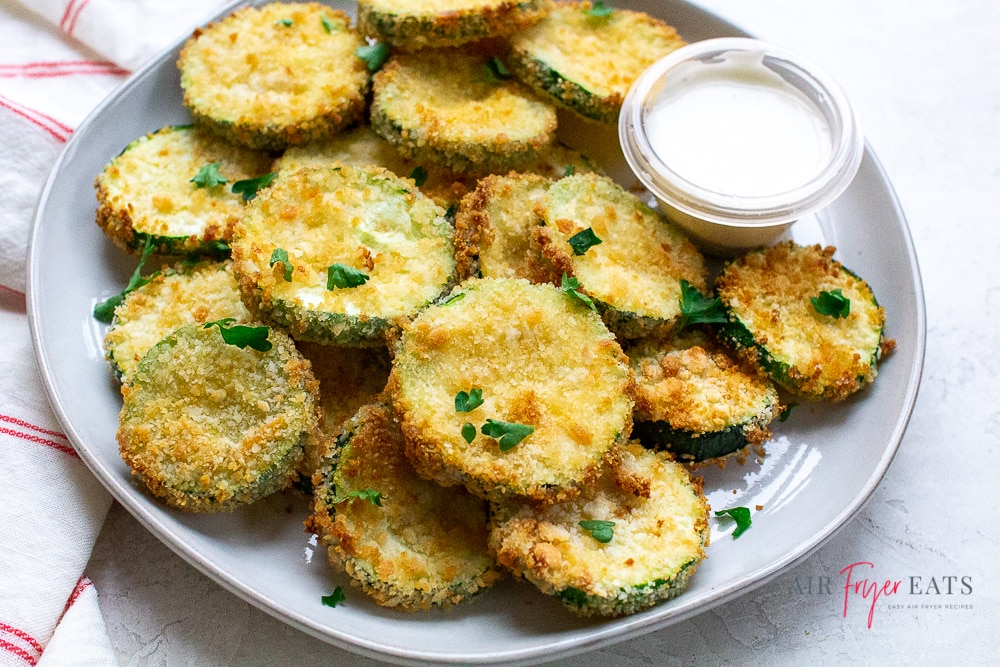 a plate of fried zucchini coins garnished with green onions and served with a white sauce