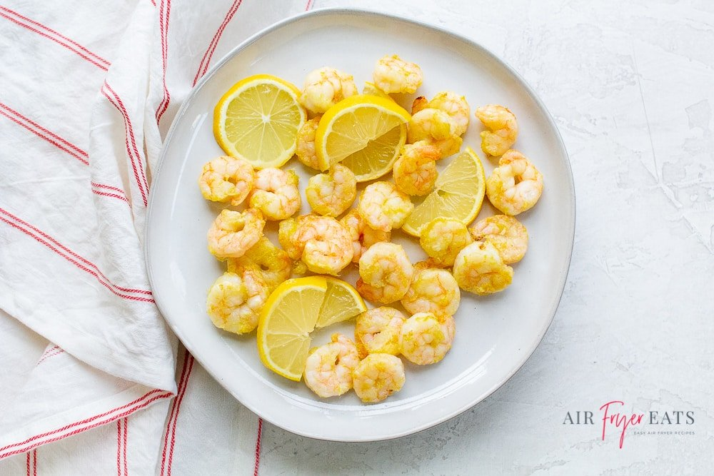 pink cooked shrimp and lemon slices on a round white plate