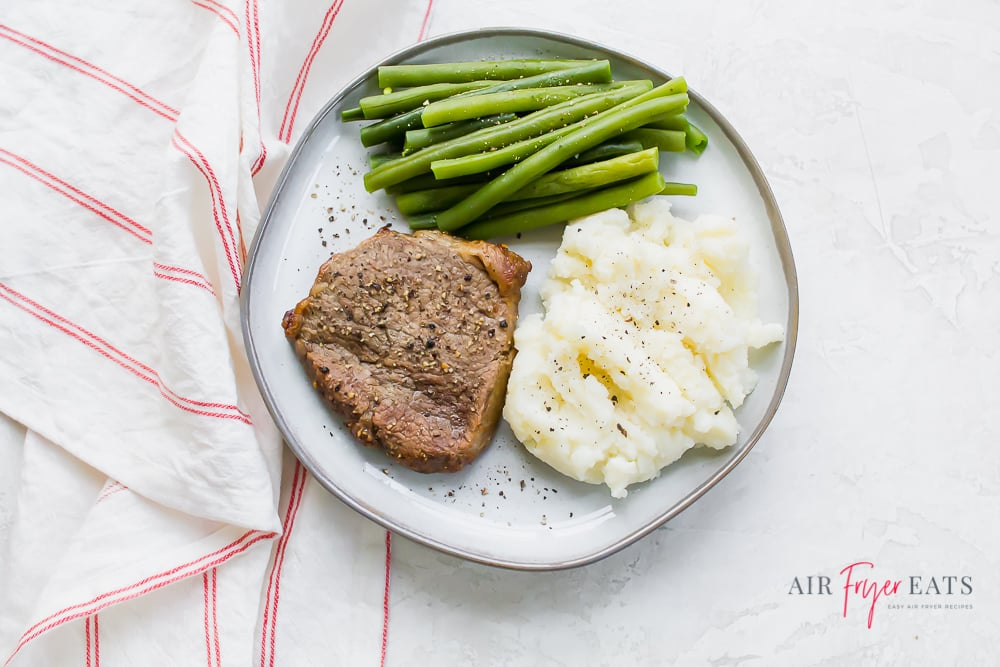 a white plate of steak, green beans, and mashed potatoes